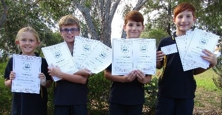 Primary Students holding certificates for breaking records at recent athletics carnival